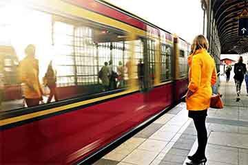 یک خانم در حال انتظار برای رسیدن قطار خود به ایستگاه است