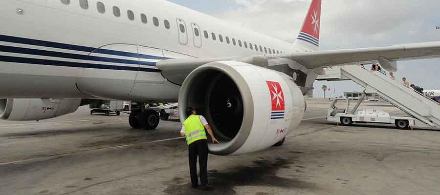 یک کارشناس مهندسی پرواز در حال چک کردن امنیت موتور هواپیما است